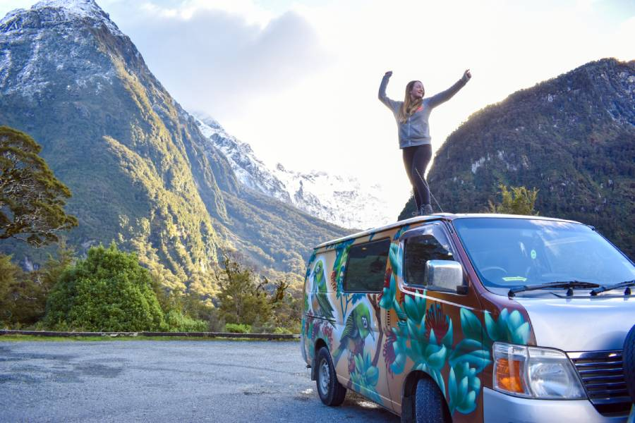 Travel blogger standing on top of a campervan in new zealand - how to make money from your travel blog